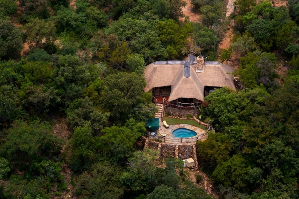 Thatched lodge with pool from above