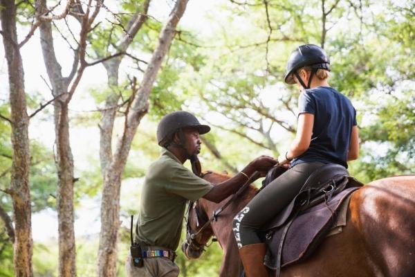 Man teaching child to horse ride