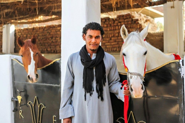 Egyptian man with 2 horses in traditional stables