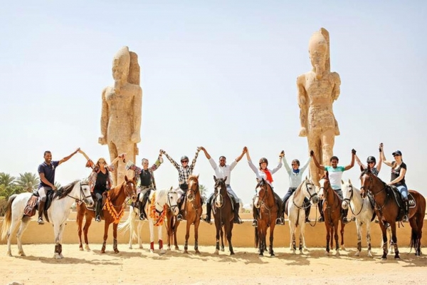 Group of horses in front of Egyptian statues