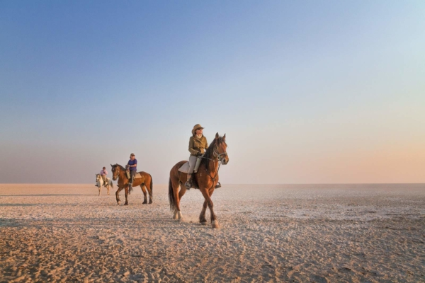 Horse riders on white salt pan with blue sky