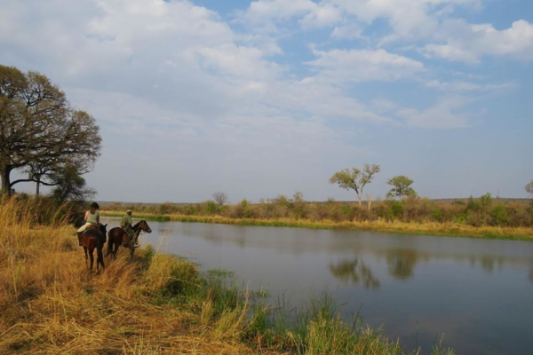 Horse riders along river