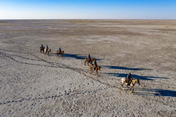 Horse riders on grey salt pans