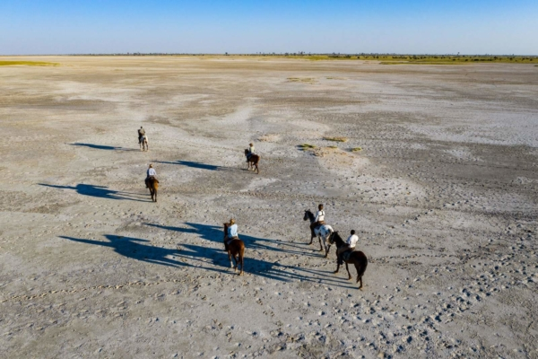 Horseback riders with shadows on white salt pan