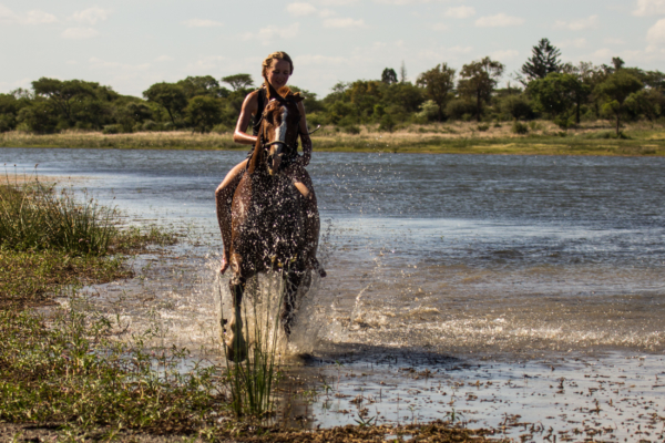 Girl on horseback galloping through water