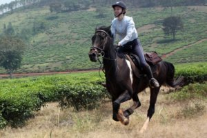 Girl on dark horse galloping through the Ugandan farmlands