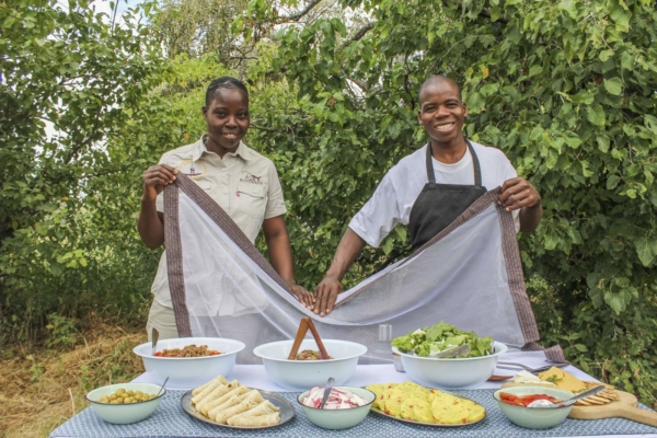 Two smiling guides serving picnic lunch