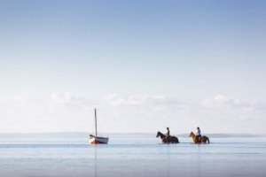 Horse riders and boat in water