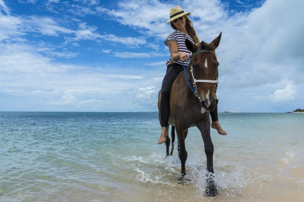 Woman riding horse bareback on beach