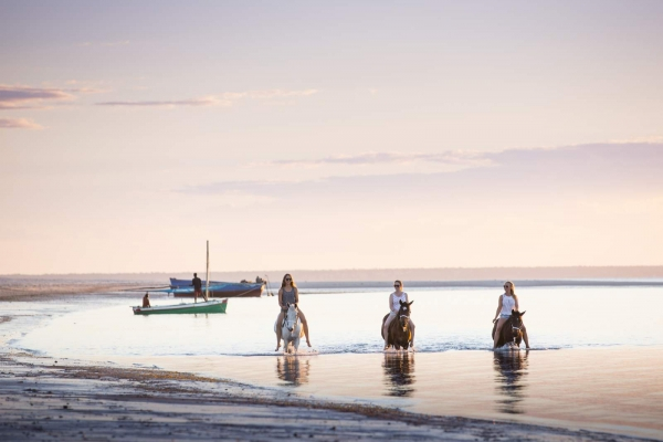 Girls riding horses bareback in ocean