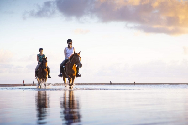 Two girls on horses walking in water