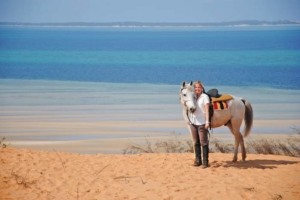 Woman with white horse on dune overlooking ocean