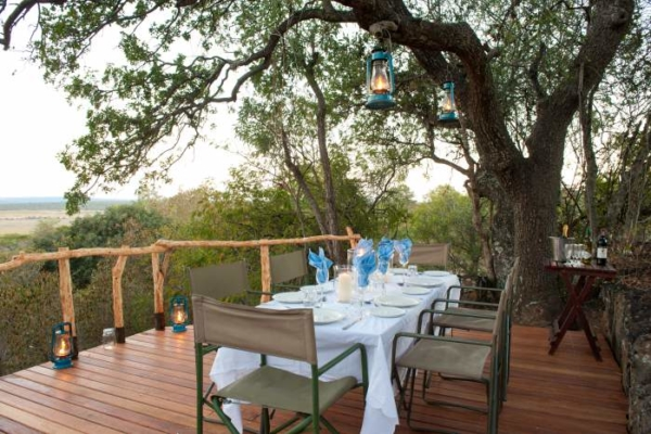 dining area on wooden deck under trees