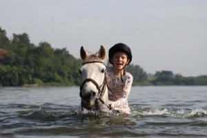 Grinning child riding horse in Nile river