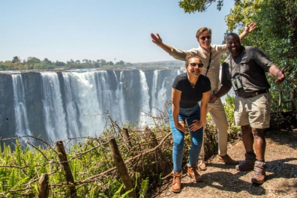 Smiling people in front of Victoria Falls waterfall