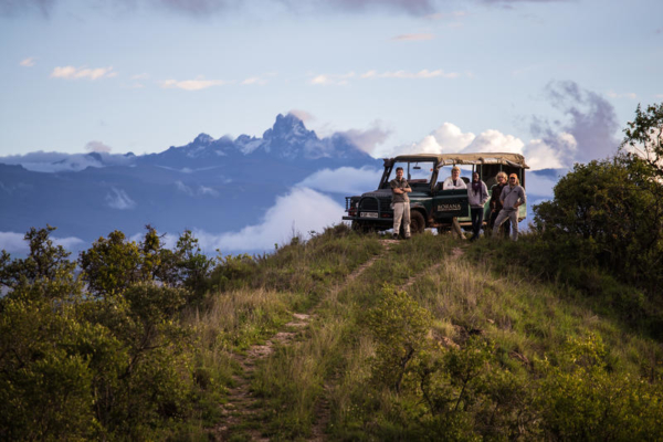 Game drive vehicle in front of mountain with clouds