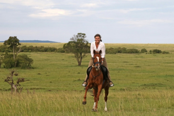Smiling woman galloping on her horse in Kenya
