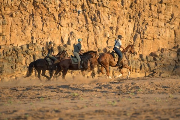 horse riders cantering in dry riverbed