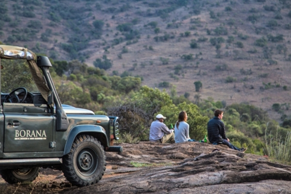 People sitting on rocks next to game drive vehicle