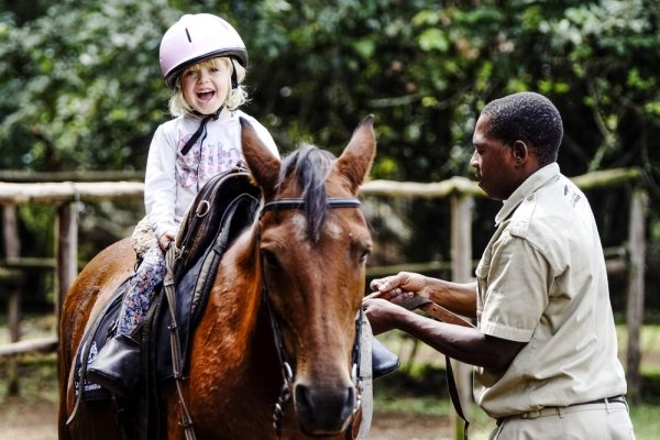 Child laughing on horse's back with man helping her ride