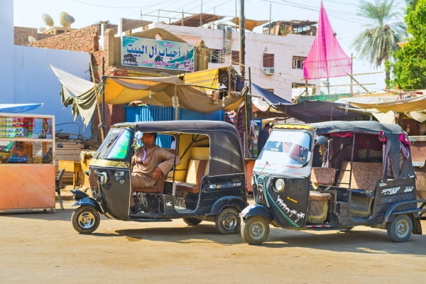 Tuktuk in Cairo with colourful signs and buildings