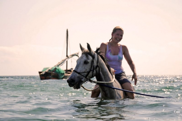 Girl on horseback in ocean with wooden boat behind