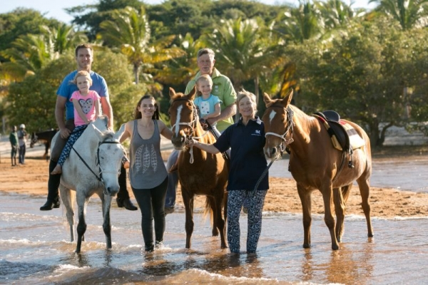 Family with horses on tropical beach