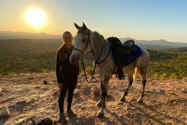 Girl with white horse on mountain at sunset