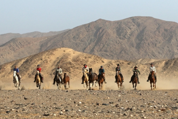 Horse riders galloping in the Namib Desert