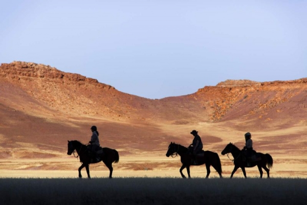 Silhouettes of horse riders in Namibia
